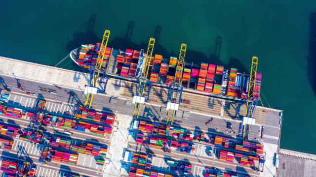 vídeos de stock e filmes b-roll de container ship loading and unloading in deep sea port, aerial view circle container shipyard business logistic import and export cargo freight ship, transportation by container ship in open sea, timelapse 4k. - circular economy