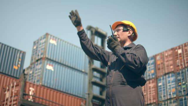 vídeos de stock, filmes e b-roll de funcionários do terminal de contêineres que trabalham em frente a pilhas de contêineres de carga coloridas e manipuladores de contêineres em segundo plano. - vinho do porto