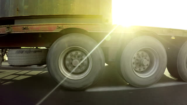 container truck highway drive with sunset sun shining - truck tire video stock e b–roll