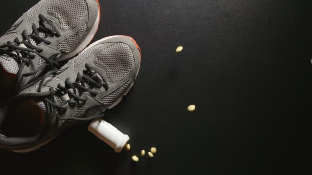 DOPING: Container with pills falls near a sneakers - slow motion, top view video