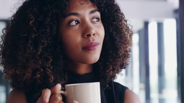 Contemplating the day ahead 4k video footage of a young businesswoman looking thoughtful while drinking coffee in an office mug stock videos & royalty-free footage