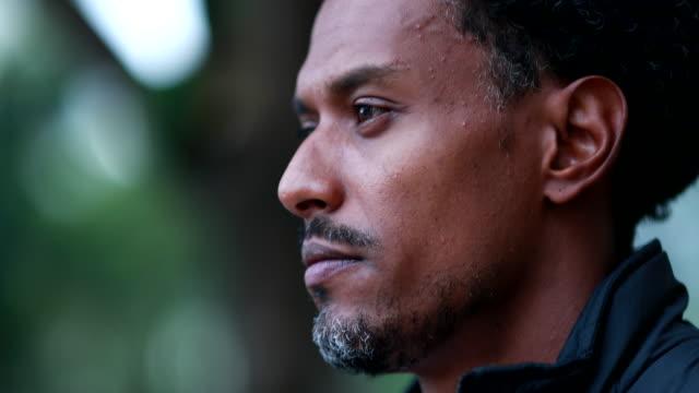 uomo contemplativo di origini africane che medita. pensieroso ritratto uomo di razza mista nero fissando - afro americano video stock e b–roll