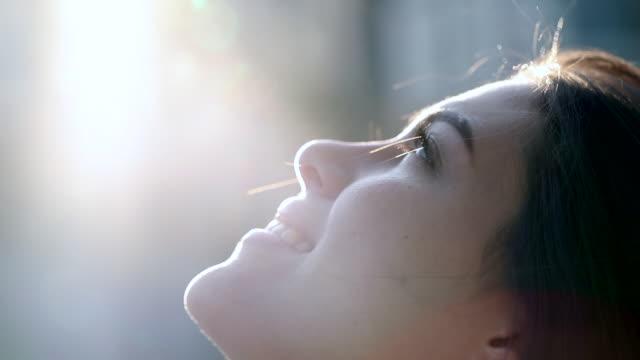信仰と希望を持って空を見上げる熟考的な若い女性。外のレンズフレアと忠実な女の子のプロフィールの顔 - 希望点の映像素材/bロール
