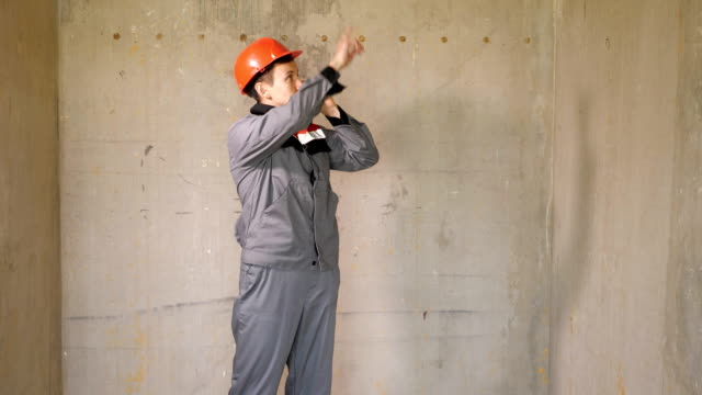 Contemporary contractor speaking on phone Adult man in hardhat speaking on smartphone while looking at clipboard and working on site handbook stock videos & royalty-free footage