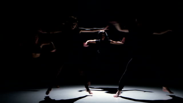 Contemporary dance performance of four dancers on black, shadow video