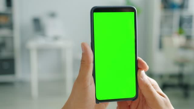 當代智慧手機與綠色螢幕在男性手在國內背景 - 模板 個影片檔及 b 捲影像