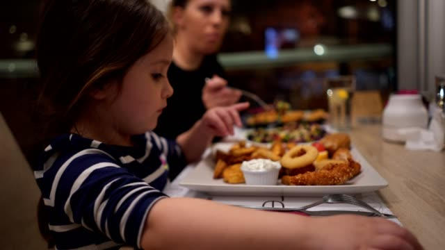 Content girl eating dinner at a restaurant with her family Cute little four year old girl eating deep fried food for dinner at a resataurant. real life stock videos & royalty-free footage