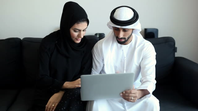 Content Middle Eastern Couple Viewing Photos and Videos on Laptop video