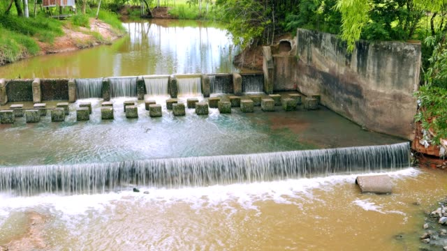 Continuous water movement scene of weir or dam to slow down the flow of water in the river. There are fresh green areas in Thailand. video