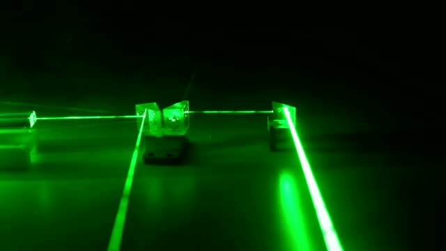 Continuous wave green laser propagates through the optical components. Laser Safety. The danger to the eye. Active medium Nd:YAG. Crystal, reflector, prism, wedge, beam in a smoke. laser stock videos & royalty-free footage