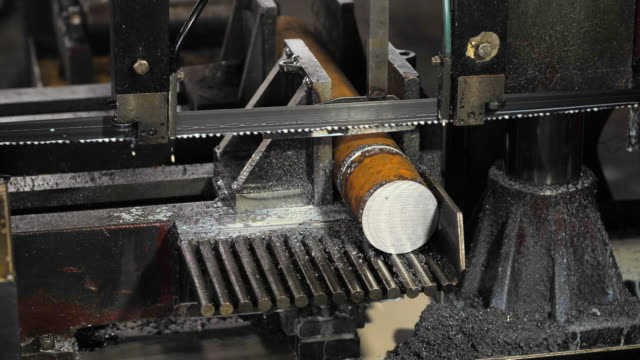 contour-bandsäge in der werkstatt. bandsägemaschinen schneiden metall, kühlemulsion wird auf die säge gegossen. - bandsäge stock-videos und b-roll-filmmaterial