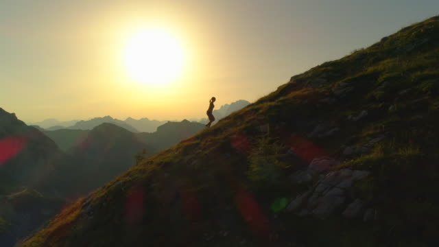 aerial silhouette: contour of young woman walking up mountain at golden lit dusk - пик стоковые видео и кадры b-roll