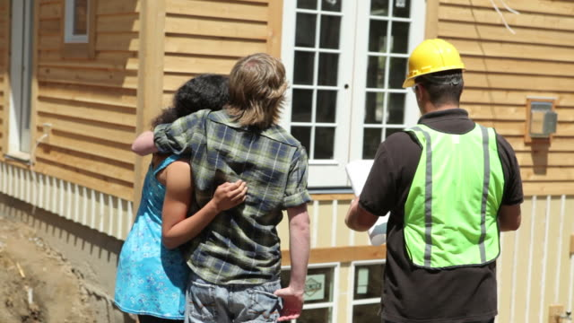 Contractor and couple look at home plans video