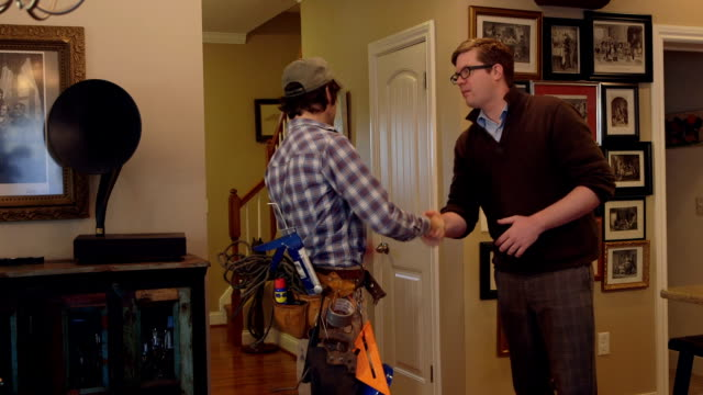 A contractor and home owner shake hands inside a house video