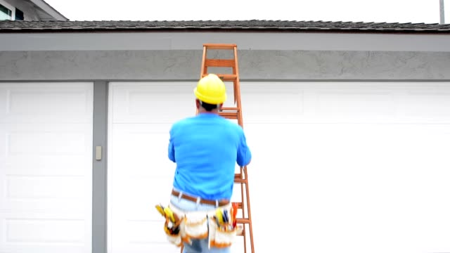 Contractor climbing ladder A contractor wearing a tool belt climbs a ladder and conducts a quick roof assessment on a residential home. quality control stock videos & royalty-free footage