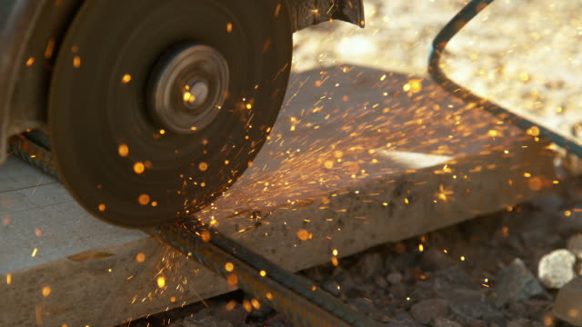 CLOSE UP: Contractor cuts into two rusty metal rods with an angle grinder. SLOW MOTION, CLOSE UP, DOF: Contractor cuts into two rusty metal rods with an angle grinder. Detailed view of laborer working at a construction site and cutting steel bars with a sharp circular saw. power tool stock videos & royalty-free footage