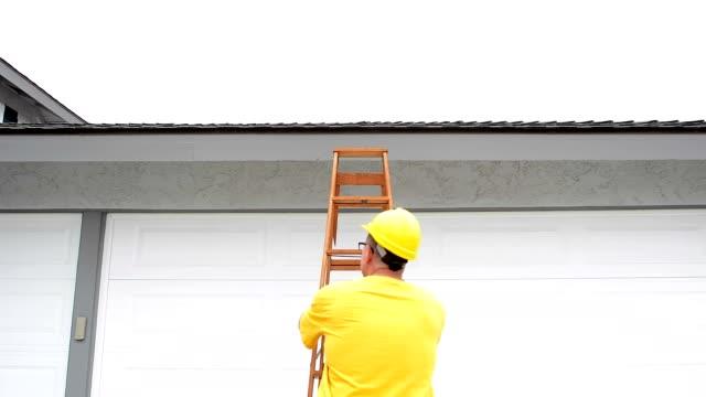 stockvideo's en b-roll-footage met contractor inspecting roof - ladder