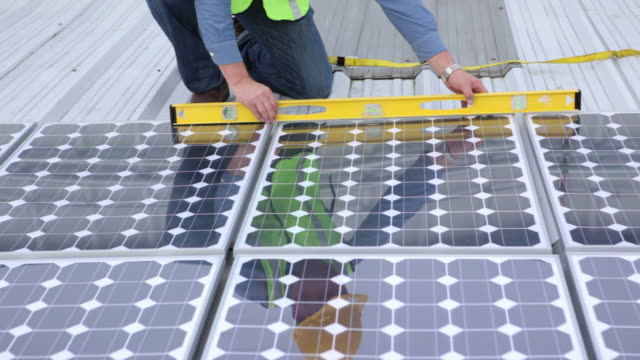 Contractor installing solar panels on industrial rooftop, portrait video