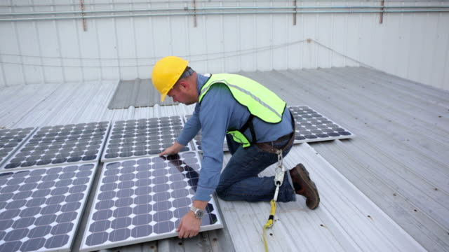 contractor installing solar panels on rooftop - solar panels stock videos & royalty-free footage