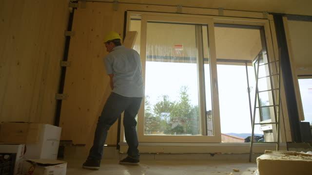 låg vinkel: entreprenören plockar upp en planka och bär den över clt huset. - solar panel bildbanksvideor och videomaterial från bakom kulisserna