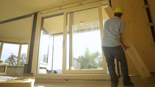 solbloss: entreprenör plockar upp en planka och bär den över clt huset. - solar panel bildbanksvideor och videomaterial från bakom kulisserna