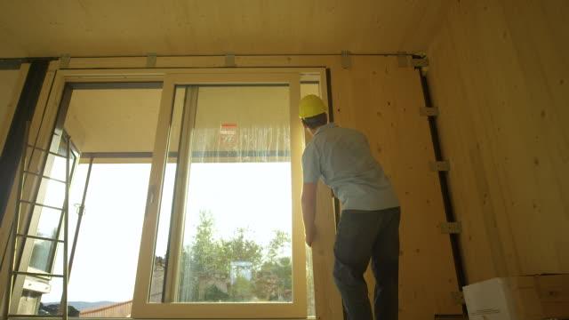 låg vinkel: entreprenör som arbetar i trähus placerar en planka bredvid glasdörr - solar panel bildbanksvideor och videomaterial från bakom kulisserna