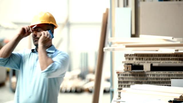 contractor yelling over cell phone. - rabbia emozione negativa video stock e b–roll