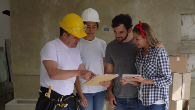 Contractors showing something on clipboard to young couple for a home renovation and ending with a handshake all smiling video