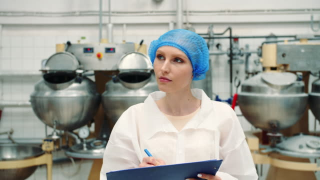 Controller checking confection factory. Candy factory Controller checking confection factory. Young female in uniform making notes in folder while inspecting laboratory in confection factory. Candy factory. quality control stock videos & royalty-free footage