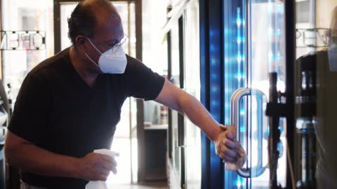 vídeos y material grabado en eventos de stock de propietario de la tienda de conveniencia usando mangos de refrigerador de limpieza de máscara durante la pandemia de covid-19 - small business