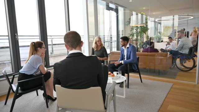 現代オフィスのビジネス同僚の会話グループ - disabilitycollection点の映像素材/bロール