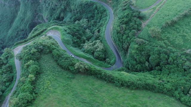 convertible vehicle follows windy mountain road - strada tortuosa video stock e b–roll