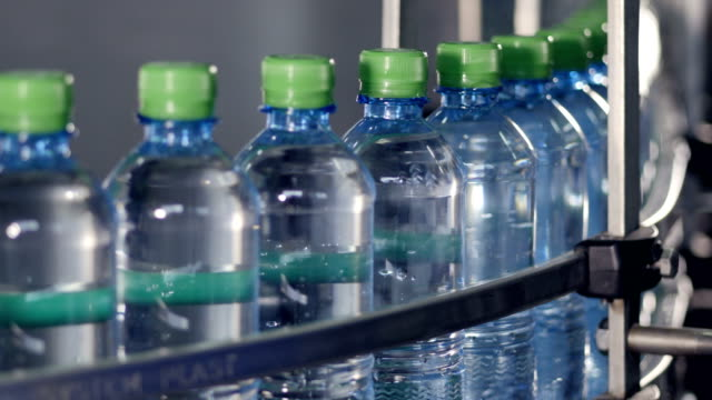 a conveyor belt full of filled and capped bottles. - coperchio video stock e b–roll