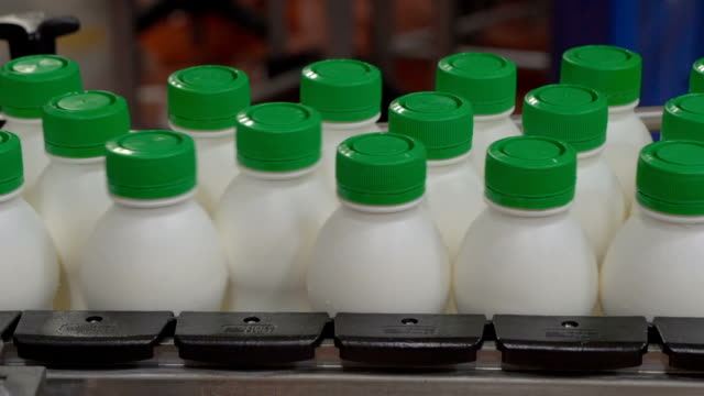 Conveyor belt in a milk factory with yogurt bottles video