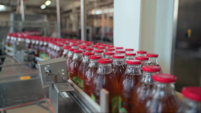 Conveyor belt, juice in glass bottles on beverage plant or factory interior, industrial manufacturing production line video