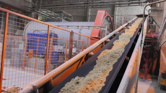 linea di nastri trasportatori in fabbrica, nastro trasportatore con sabbia e sfere metalliche - cemento video stock e b–roll