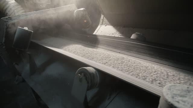 コンベア ベルトが荷重を工場からペレットを輸送します。ほこりに光 - セメント点の映像素材/bロール