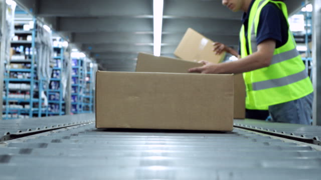 Conveyor Belt with Boxes Boxes on a conveyor belt in a warehouse.  The boxes move down the conveyor belt and workers take them off.  It's a distribution warehouse, you can see product on shelves in the background.  One of the workers is an African American woman and the other is a hispanic man. warehouse stock videos & royalty-free footage