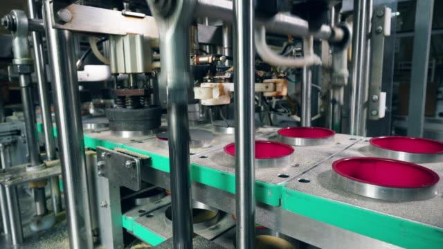 conveyor är att sätta folie locket på containrar på en livsmedels fabrik. - biltransporttrailer bildbanksvideor och videomaterial från bakom kulisserna