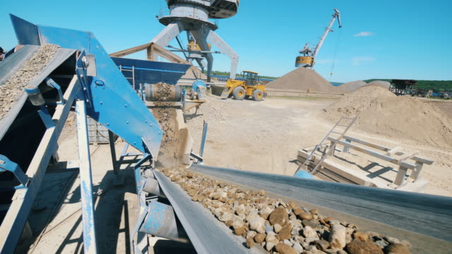 Conveyor moves rubble while sorting it. Mining equipment working.