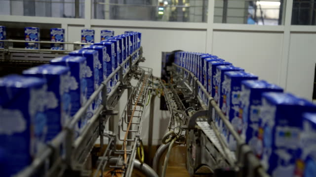 Conveyor with milk tetra packaging. Factory for bottling of dairy products. Dairy products are moving on conveyor - video