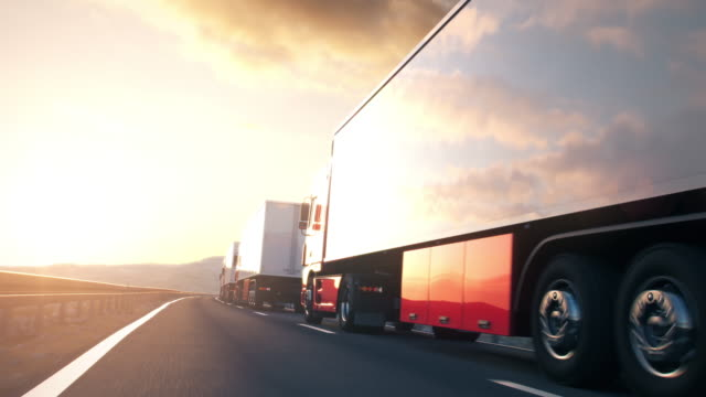 convoy of semi-trailer trucks driving into the sunset