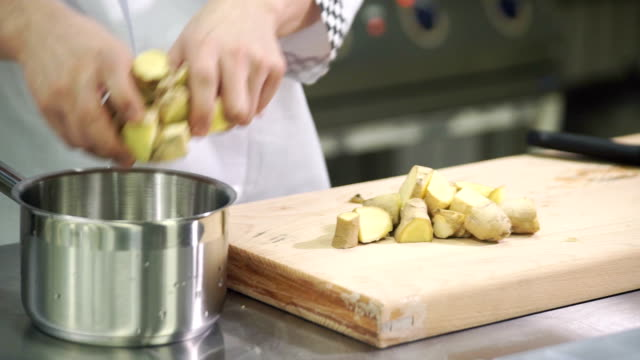 Cook adds coarsely chopped ginger root in pot in industrial kitchen video