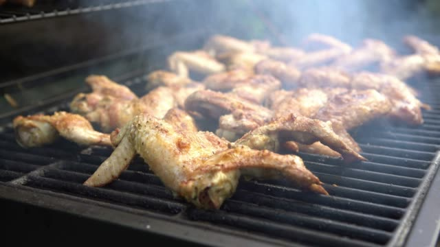 4K, Cook barbecue with delicious chicken wings on grilled meat. Grilling BBQ
