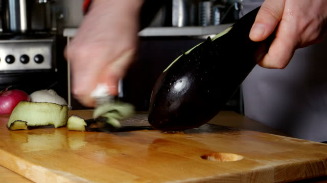 cook clean un melanzana su un tagliere di cucina - melanzane video stock e b–roll