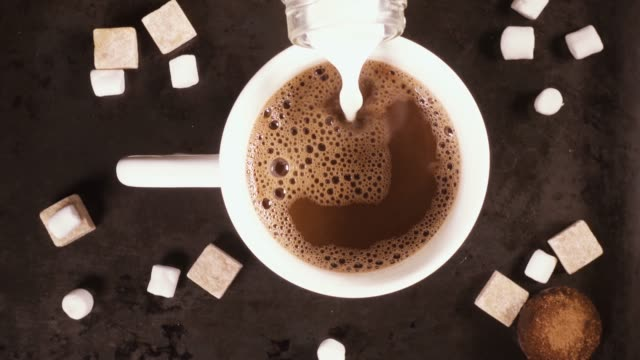 Cook cocoa or hot chocolate in a white mug top view In ready hot chocolate cocoa coffee pour milk from a glass bottle top view mug stock videos & royalty-free footage