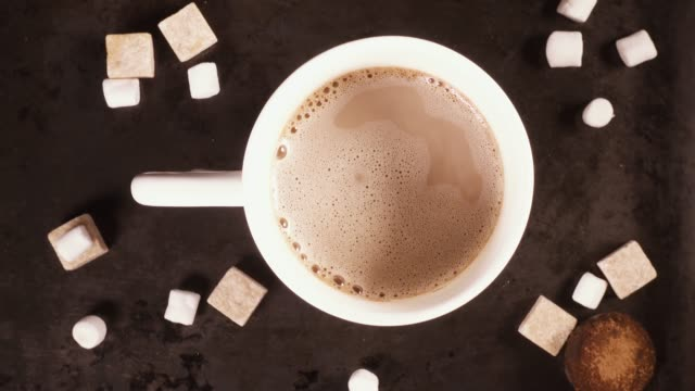 Cook cocoa or hot chocolate in a white mug top view Pour out marshmallows from the palm of your hand in a white mug with hot chocolate cocoa coffee on a gray background top view marshmallow stock videos & royalty-free footage