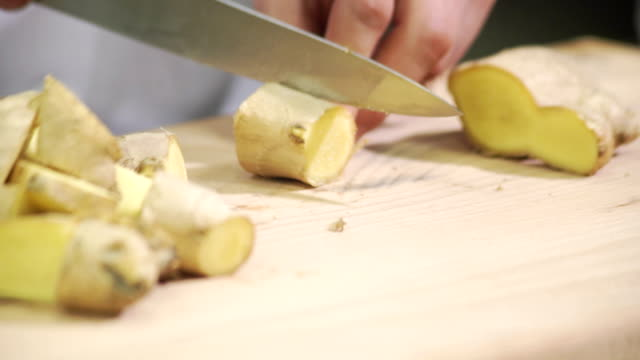 Cook cuts into cubs ginger on wooden board inside industrial kitchen video