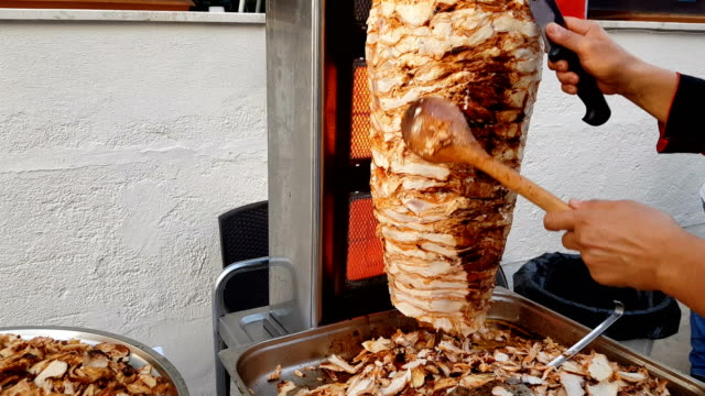 a cook cuts meat on a skewer to make shawarma. turkish doner-kebab - spiedino video stock e b–roll