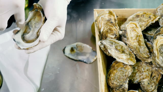 Cook cuts the oyster inside the shell video